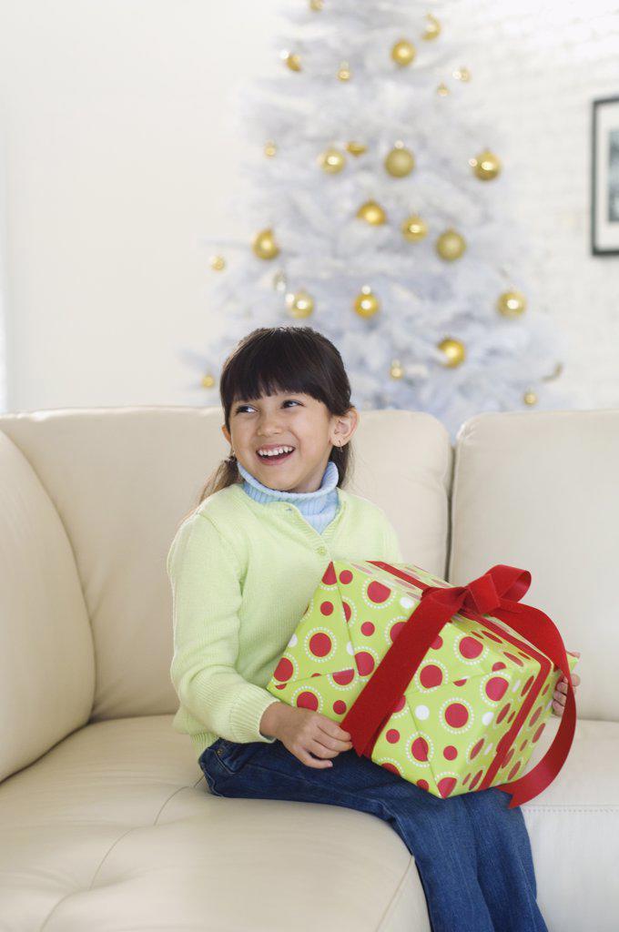 Hispanic girl holding Christmas gift : Stock Photo