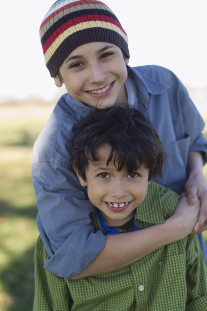 Hispanic brothers hugging outdoors : Stock Photo