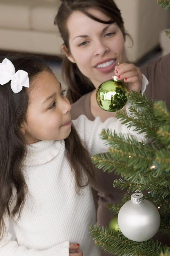 Stock Photo: 1589R-37243 Hispanic mother and daughter decorating Christmas tree