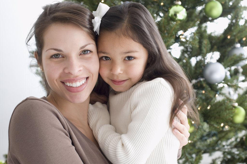 Stock Photo: 1589R-37244 Hispanic mother and daughter hugging next to Christmas tree