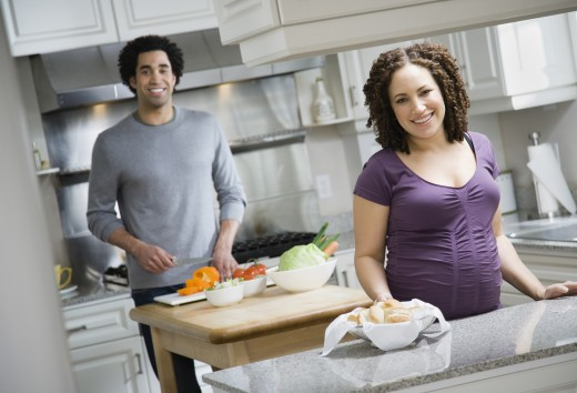 Stock Photo: 1589R-37397 Pregnant African couple preparing food