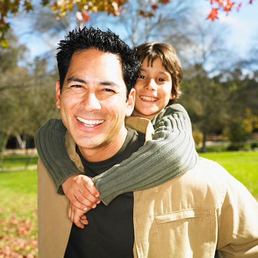 Mixed Race father giving son piggyback ride in park : Stock Photo