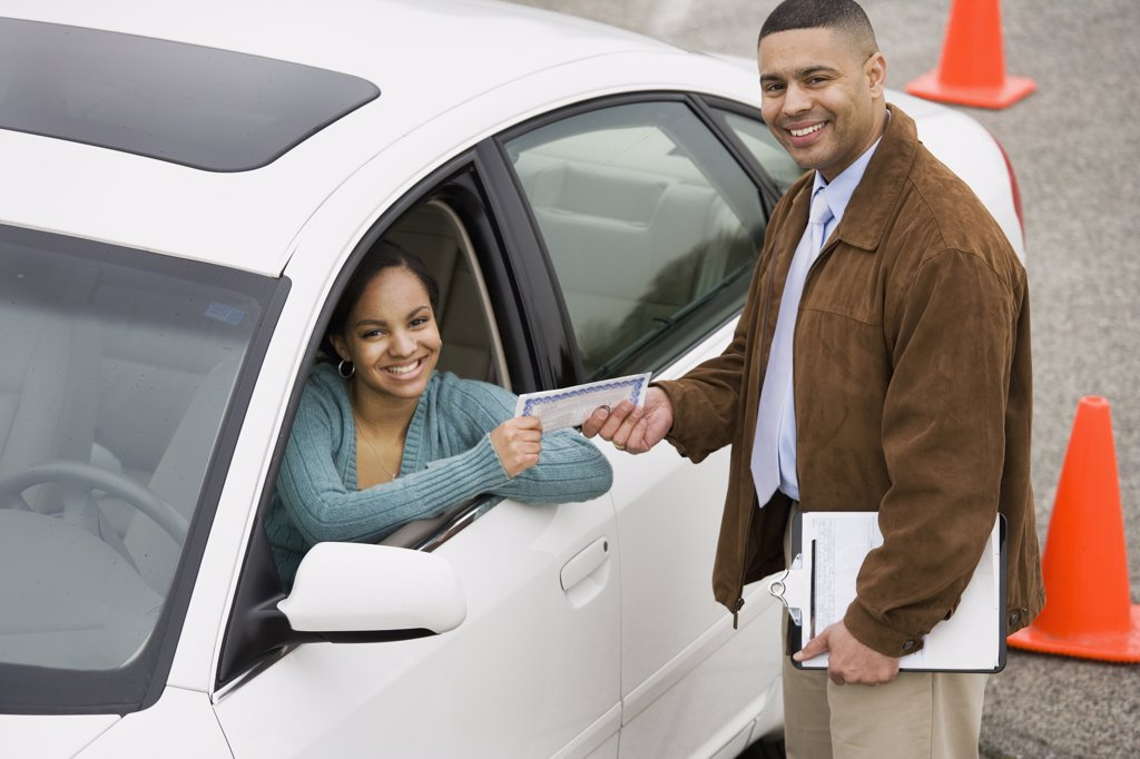 Stock Photo: 1589R-37690 African teenager receiving drivers test certificate
