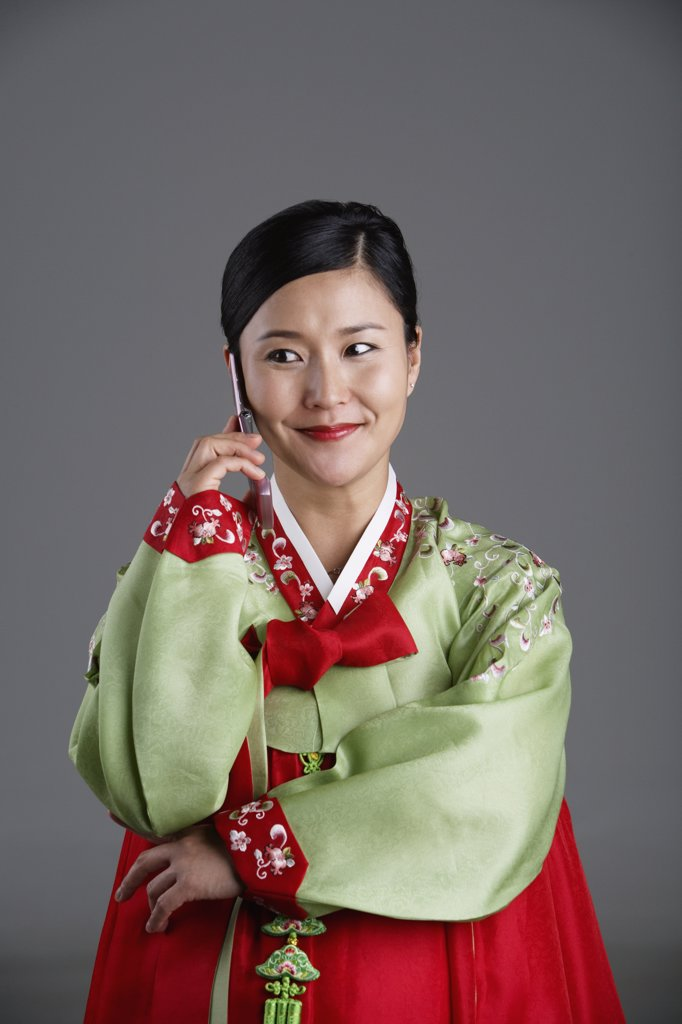 Stock Photo: 1589R-37887 Korean woman in traditional dress talking on cell phone