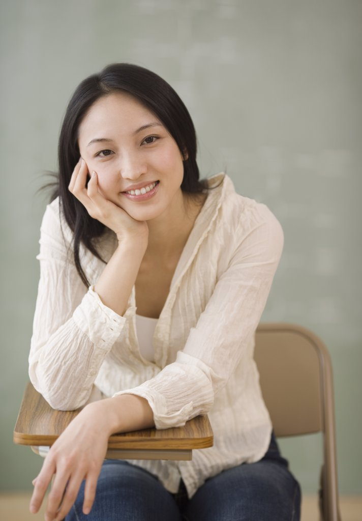 Stock Photo: 1589R-37914 Asian woman sitting at school desk