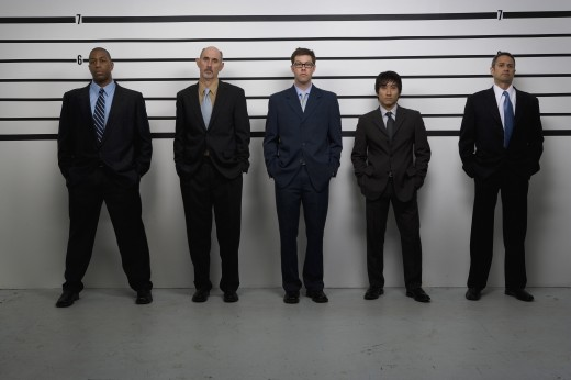 Multi-ethnic businessmen in police line up : Stock Photo