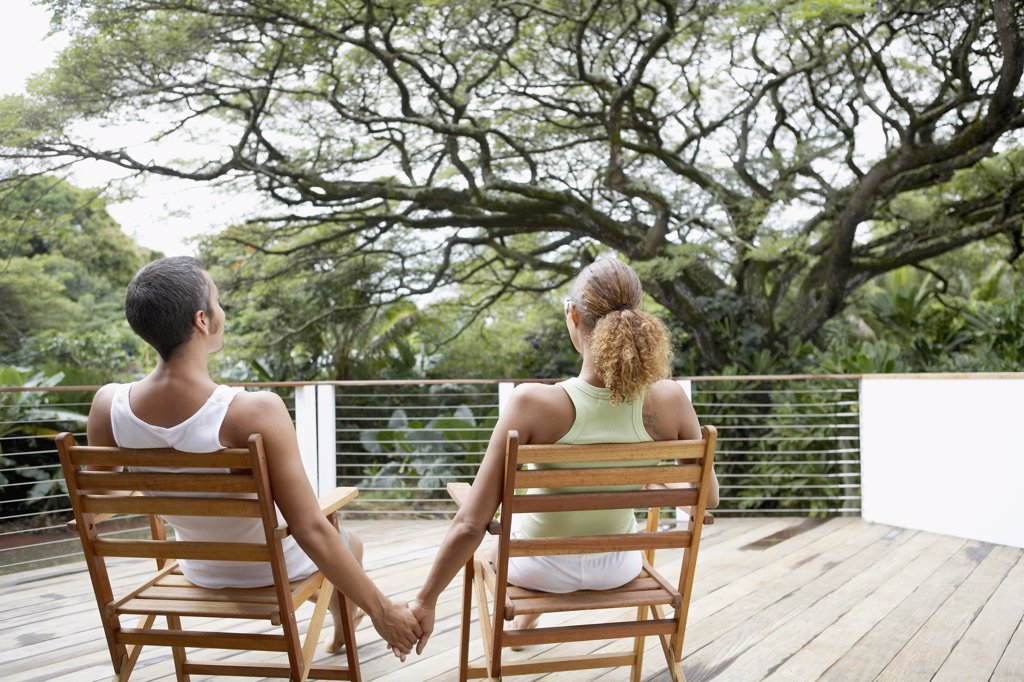 Multi-ethnic couple sitting on deck : Stock Photo