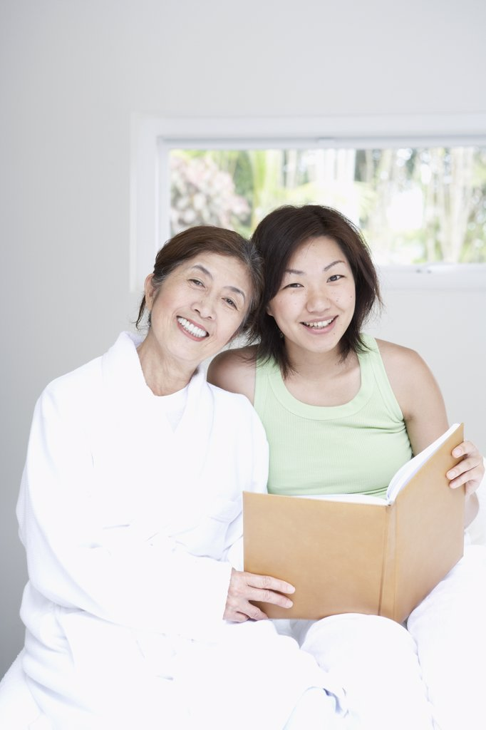 Asian mother and adult daughter looking at photo album : Stock Photo
