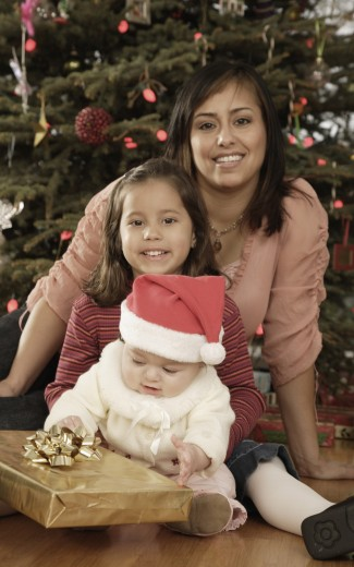 Hispanic mother and children in front of Christmas tree : Stock Photo