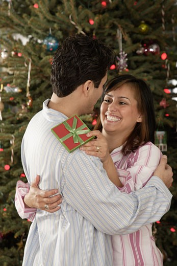 Hispanic couple hugging on Christmas : Stock Photo