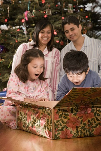Hispanic siblings opening Christmas gift : Stock Photo