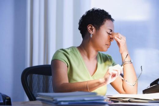 African businesswoman rubbing eyes : Stock Photo