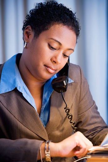 Stock Photo: 1589R-38478 African businesswoman checking watch