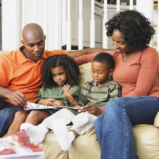 Stock Photo: 1589R-38546 African American family reading on sofa