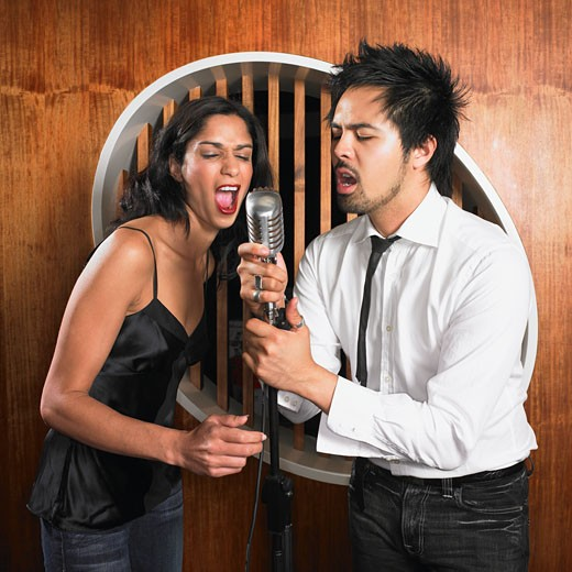 Stock Photo: 1589R-38612 Multi-ethnic couple singing into microphone