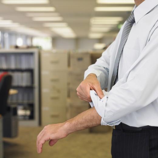 Hispanic businessman rolling up sleeve : Stock Photo