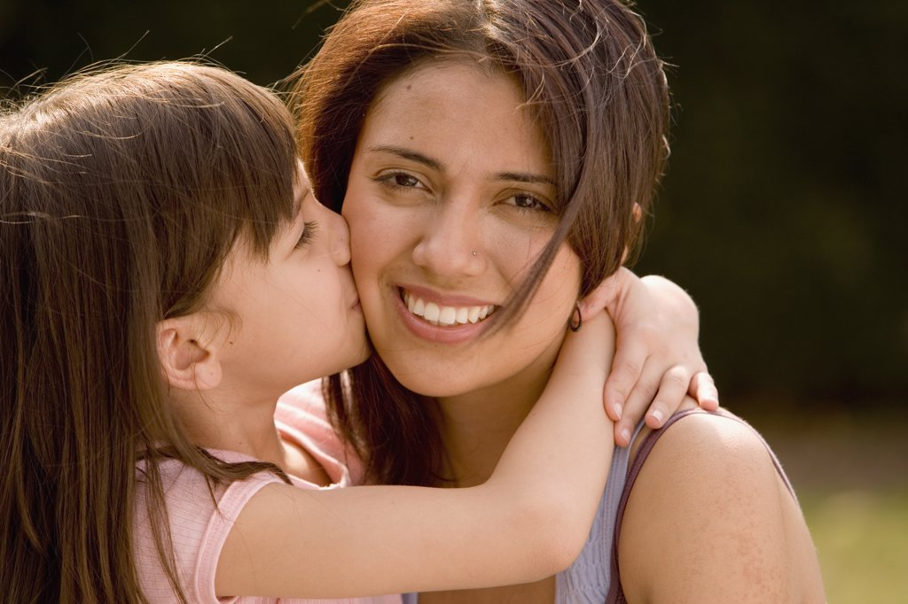 Hispanic girl kissing mother on cheek : Stock Photo