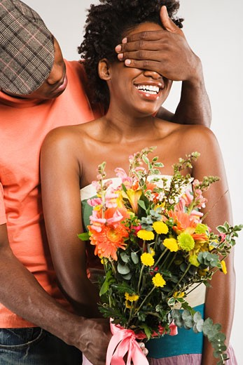 African American man surprising girlfriend with flowers : Stock Photo