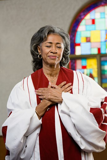 African American female Reverend with hands on heart : Stock Photo