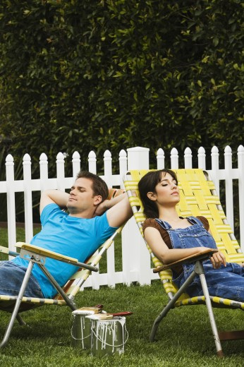 Multi-ethnic couple relaxing in lawn chairs : Stock Photo