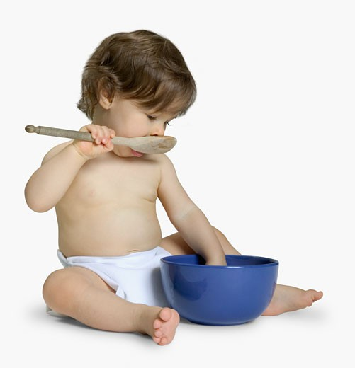 Baby playing with bowl and spoon : Stock Photo