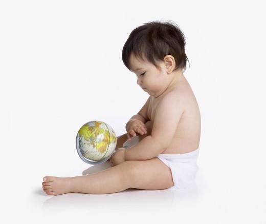 Studio shot of Hispanic baby holding globe : Stock Photo