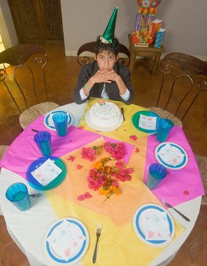 Stock Photo: 1589R-39269 Hispanic boy alone with birthday cake