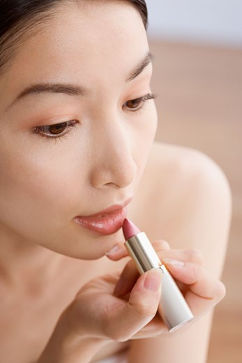 Asian woman applying lipstick : Stock Photo