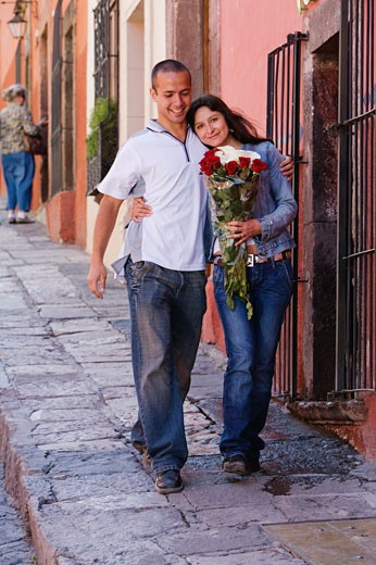 Stock Photo: 1589R-39515 Hispanic couple on sidewalk with roses