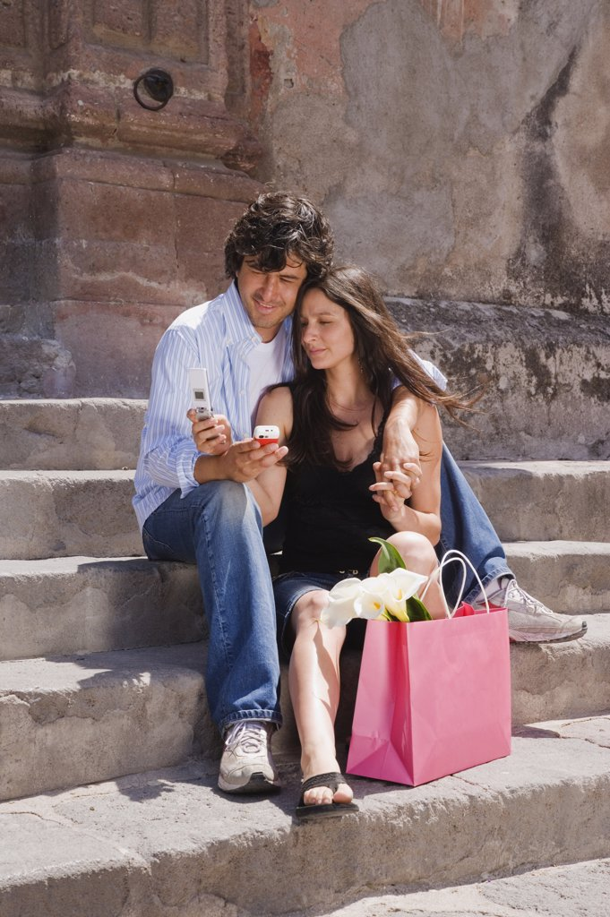 Stock Photo: 1589R-39529 Hispanic couple looking at cell phones