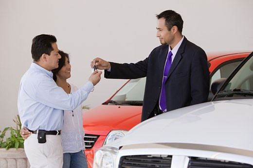 Hispanic couple taking keys from car salesman : Stock Photo