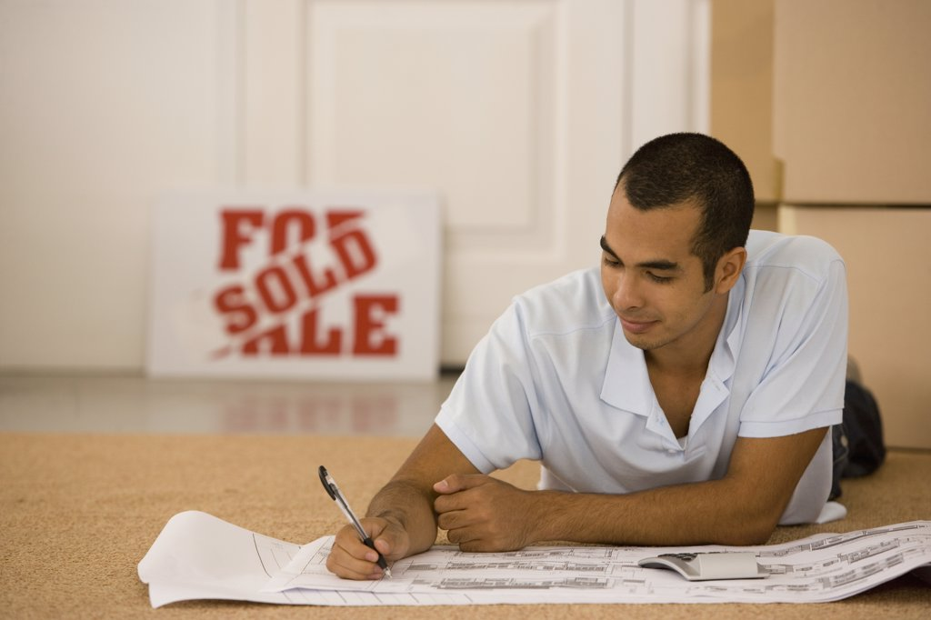 Stock Photo: 1589R-39738 Man writing on blueprints in new house