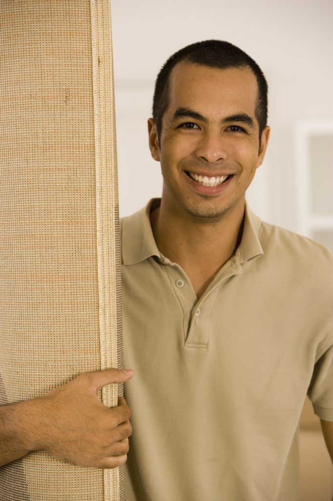 Stock Photo: 1589R-39752 Young man holding rolled rug