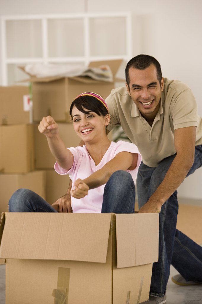 Stock Photo: 1589R-39753 Man pushing wife in moving box