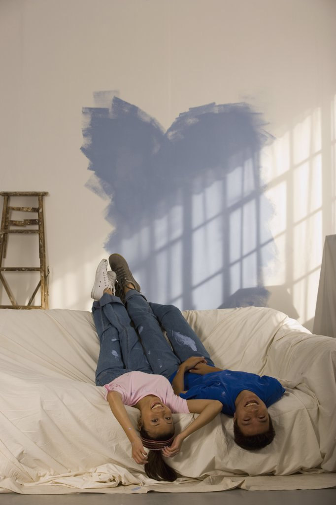 Asian couple in partially painted room : Stock Photo