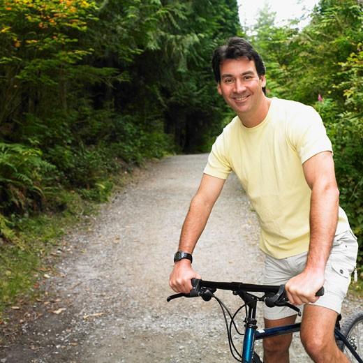 Man riding bicycle on nature trail : Stock Photo