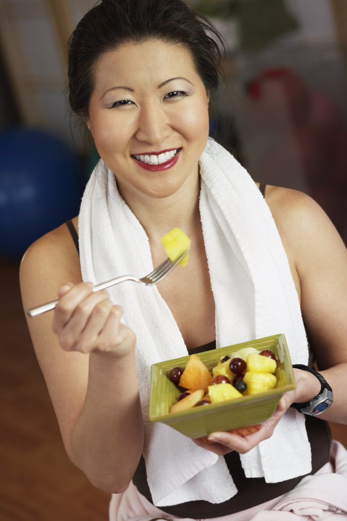 Stock Photo: 1589R-40430 Asian woman eating fruit