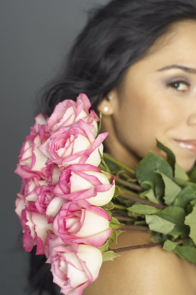 Hispanic woman holding bouquet of flowers : Stock Photo