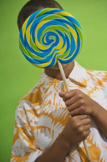 Stock Photo: 1589R-40961 African boy holding big lollipop over face
