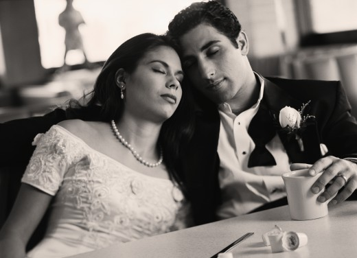 Stock Photo: 1589R-40992 Bride and groom with eyes closed at diner
