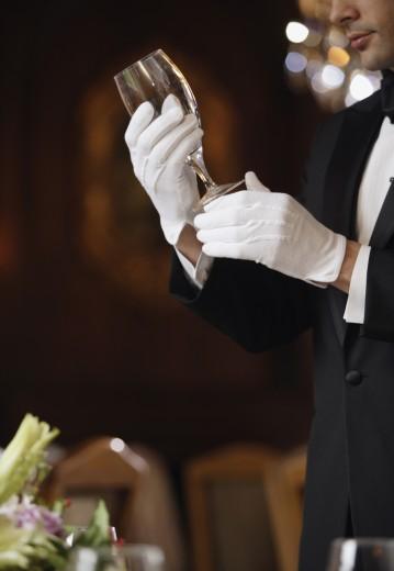 Stock Photo: 1589R-41003 Hispanic male waiter examining wine glass