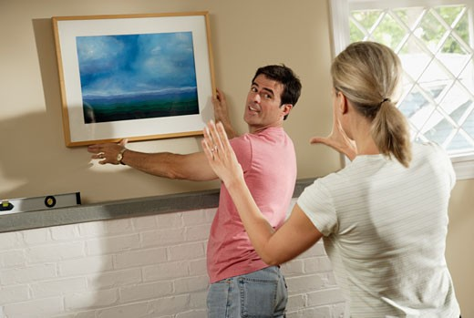 Couple hanging artwork over mantle : Stock Photo