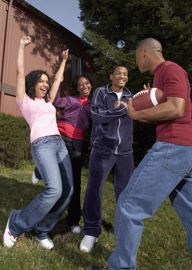 Multi-ethnic friends playing football : Stock Photo