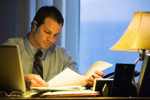 Stock Photo: 1589R-41173 Hispanic businessman reading paperwork