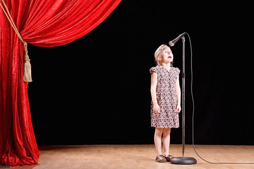Girl speaking into microphone on stage : Stock Photo