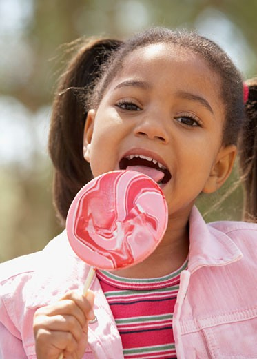 Stock Photo: 1589R-41237 African American girl eating lollipop
