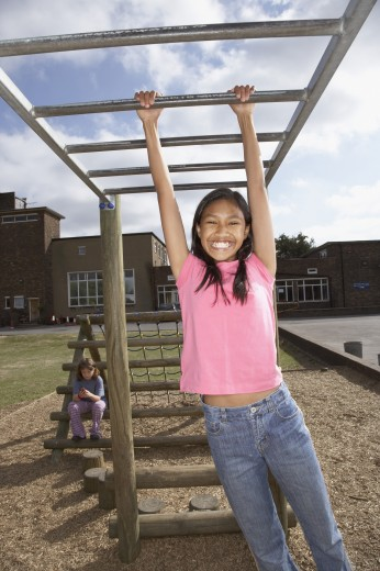 Stock Photo: 1589R-41422 Pacific Islander girl hanging on jungle gym