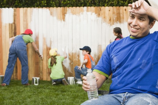 Mixed Race family painting fence : Stock Photo