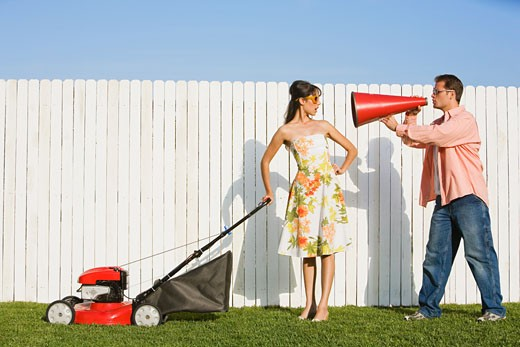 Man yelling at wife pushing lawn mower : Stock Photo