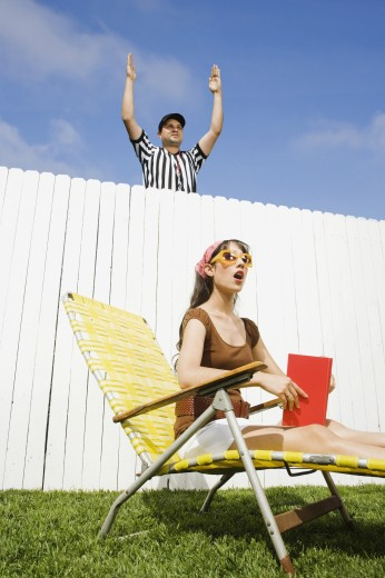 Hispanic referee making call over fence : Stock Photo